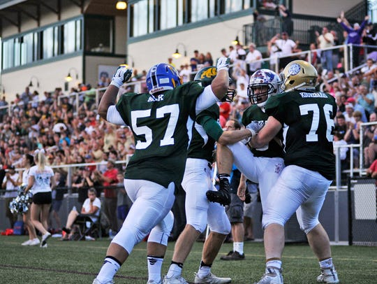Vermont's Dylan Ellis is mobbed by teammates after