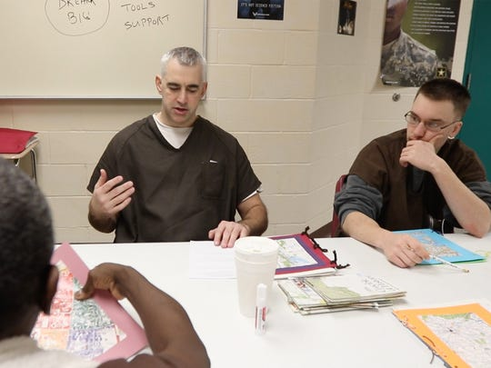 Jerry Stearns discusses a book he read while fellow inmates Phillip Gambino and Paul Brownlee, back to camera, listen during the Veterans Outreach Center's art therapy class held in the veterans unit of the Monroe County Jail.  Stearns served with the U.S. Navy, Gambino, U.S. Airforce, and Brownlee with the U. S. Army.