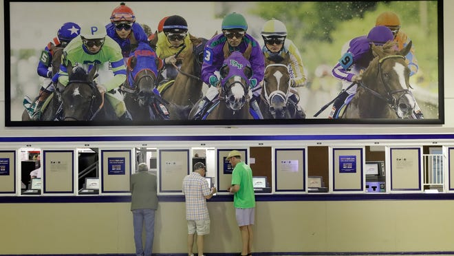 Fans place bets ahead of a horse race at Pimlico in Baltimore.