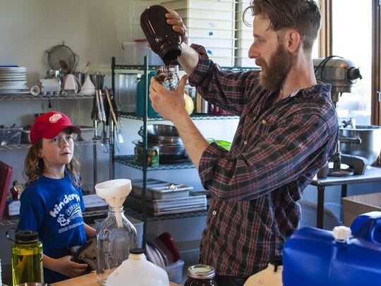 Henry Dorman, 9, left, watches Mike Proia of the Blank Page Cafe make chocolate milk at Bread and Butter Farm in Shelburne on Friday, May 20, 2016. Bread and Butter Farm encompasses several small enterprises under one roof.