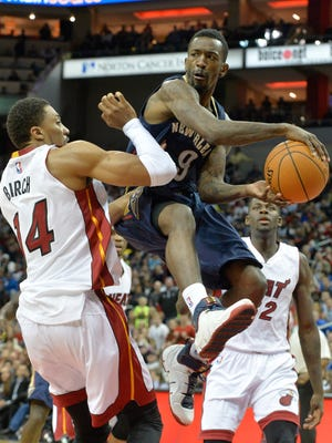 New Orleans Pelicans' Russ Smith, center, passes the ball around the defense of Miami Heat's Khem Birch during the third quarter of an NBA basketball preseason game in Louisville, Ky., Saturday, Oct. 4, 2014. New Orleans defeated Miami 98-86. (AP Photo/Timothy D. Easley)