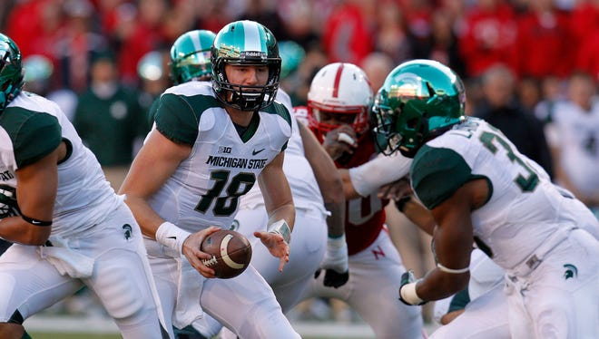 Michigan State quarterback Conner Cook (18) readies to hand off to running back Jeremy Langford (33) in the second quarter Saturday at Memorial Stadium.