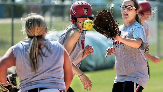 Tipton Rosemark Academy's Charli Rice (right) and catcher Shelby Clifton (left) chase down runner Abby West during drills Wednesday. The Rebels are a legitimate title contender in a sport Memphis typically doesn't have a lot of success in.
