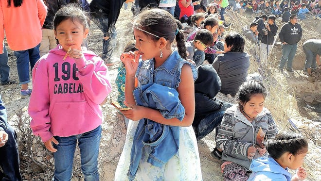 Two young girls sample the mescal along with the rest of the community and students. Mescal leaves have a comparable food value to oats. The roasted rosette hearts have thick fleshy leaves that are peeled back like an artichoke and eaten.