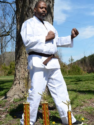 John J. Jones poses with three trophies he won recently at a karate competition in Salisbury, Md. in February. Jones, a brown belt, has been practicing martial arts for decades.