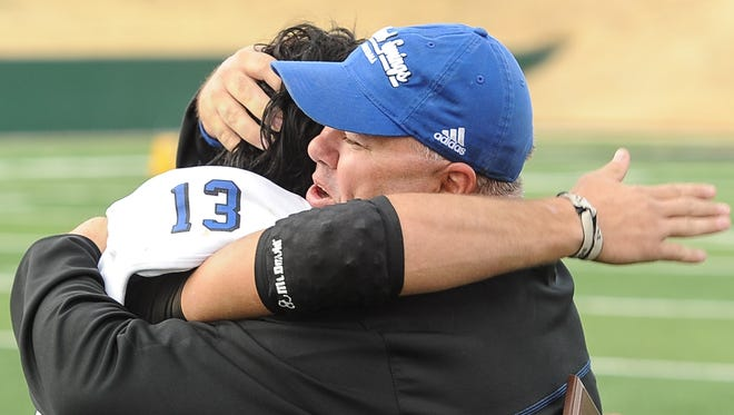 Richland Springs head coach Jerry Burkhart hugs spread back Chance Bush after the Coyotes' win over Follett in the 2012 state final.