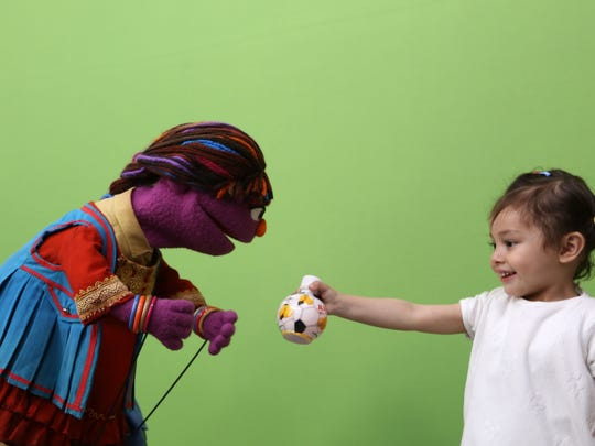 In this Thursday, April 7, 2016, photo, Sesame Street's new character, a sassy, fun 6-year-old Afghan puppet girl called Zari, left, interacts with a child during a recording session ahead of her television debut on Afghanistan's local production of the show in Kabul.
