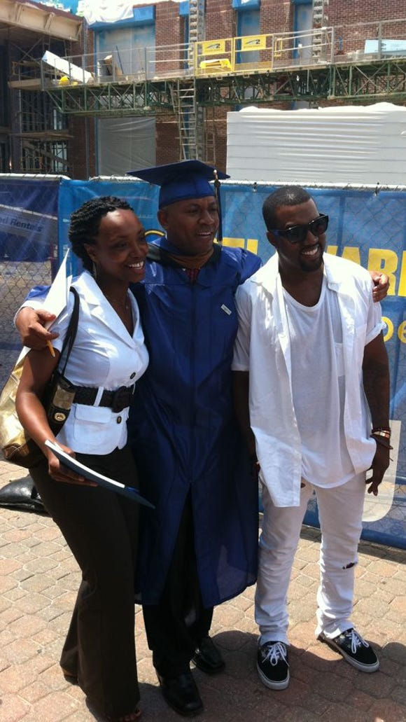 Kanye West (right) poses with his cousin Andre and an unknown woman at the University of Delaware commencement in Newark in May 2011.