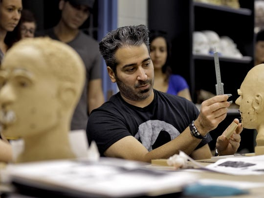 Forensic artist Joe Mullins of the National Center for Missing and Exploited Children works with fellow artists on facial reconstructions Wednesday at the University of South Florida in Tampa.