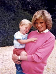 Princess Diana holds Prince William while pregnant