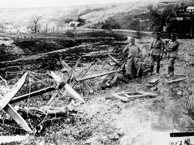 German soldiers survey the death and destruction along a barbed wire fence during World War I. Date and location are unknown. (AP Photo)