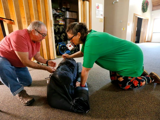 John and Elaine Forrest, volunteers with Steping Stones through Blackman United Methodist Church roll up an inflatible bed that they use with the program on Thursday, Dec. 7, 2017.