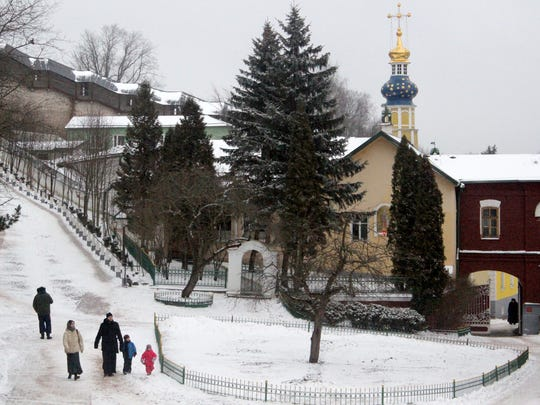 A family descends the steep Bloody Path to attend Orthodox services inside the Pskov Caves Monastery.
