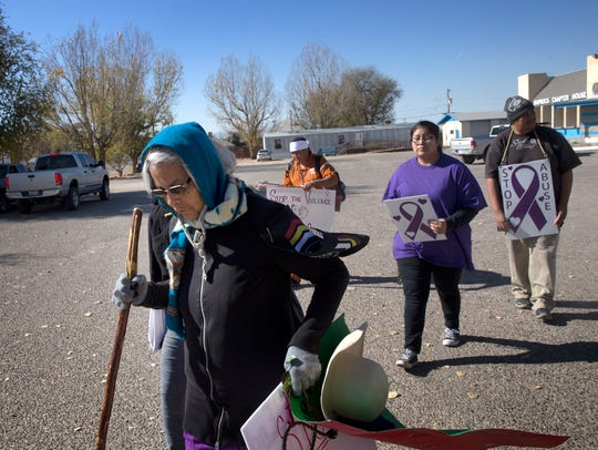 Ema Thompson, left, is joined by supporters Efrem John, Rhea Benally and Ouray D. Benally Thursday after completing a walk to the Shiprock Chapter house.