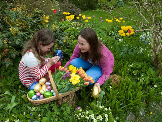 Easter egg hunt Young girls with chocolate eggs and Spring flowers
