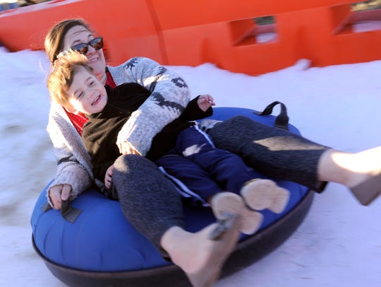 Garrett Irons, 3, rides down a hill of man-made snow Friday during the first Dyess Air Force Base Winterfest. Leslie Ballard, a friend of his family, rode along with him.