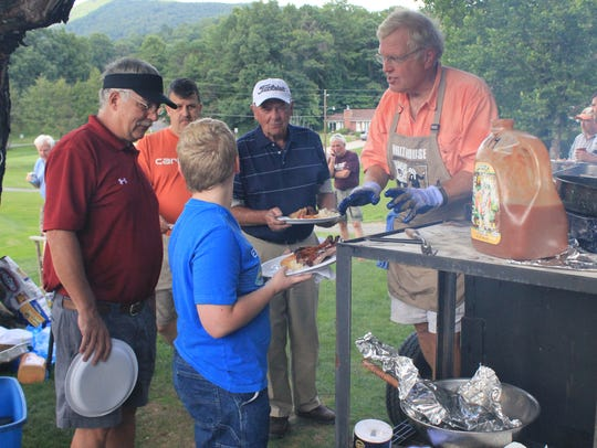 Mayor Michael Sobol serves barbecue fresh from the
