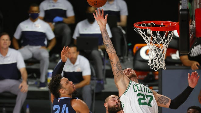 Boston Celtics center Daniel Theis (right) battles for the basketball during the first half of an NBA basketball game without fans against the Memphis Grizzlies on Aug. 11, 2020, in Lake Buena Vista, Fla.