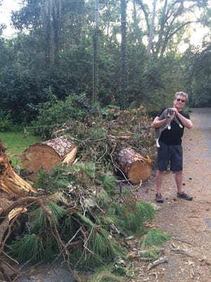Mark Sager and cat Tio Tango stand next to the pine tree that feel on the Sager home during Hurricane Hermine.