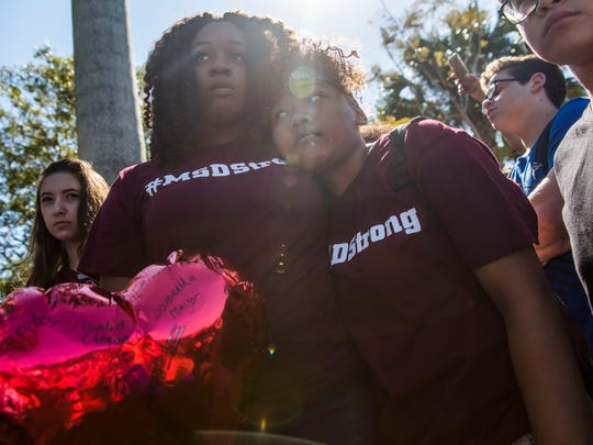 Mei-Ling Ho-Shing, left, and Erin LaVoix listen to speakers at Pine Trails Park in Parkland, Fla., during the National School Walkout on Wednesday, March 14, 2018.