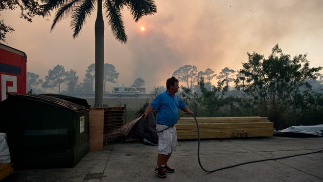 """American Stairs employee Jeff Spencer, of Palm City, wets down lumber and brush lining the businesses' property Wednesday, Feb. 15, 2017, on Southwest Old Kansas Avenue as a brush fire burns behind him across Florida's Turnpike in Martin County. """"I'm protecting my welfare, and my kitty,"""" Spencer said, referring to a cat that lives near the business. Multiple fires were aided by windy conditions across Martin and St. Lucie counties."""