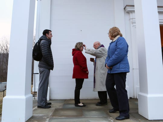 The Rev. Daniel Ramm distributes ashes to workers from
