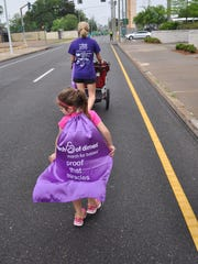 Frannie Beebe walks with four-year-old Amelia while pushing one-year-old twins Jake and Pearce and three-year-old Drew in a stroller during the Alexandria March for Babies. The annual walk benefits the March of Dimes organization, which supports families with premature babies and funds research to prevent early births. Beebe's three sons all were born premature and spent weeks in the newborn intensive care unit.