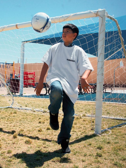 """Bill Armendariz - Headlight Photos   Andy Lerma, 10, practices his ball handling skills with new soccer balls donated to Bell Elementary School students on Tuesday by the American Legion Auxiliary Unit 4. The Auxiliary's donation was made possible from donors they contacted through the 'Kick for Nick"""" campaign. Army PFC Nick Madaras had a passion for soccer and was killed in action in Iraq in 2006."""