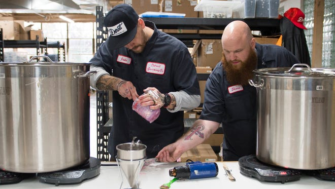 Jake Krusen, Detroit Grooming Co. lab manager and Shaun Walford, cofounder, work on a batch of soap at its Ferndale headquarters on Thursday, Nov. 9, 2017.