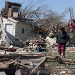 Ann Schabacker searches for her scattered belongings after her home was destroyed by a tornado on April 10 in Rochelle, Ill. At least two tornadoes swept through Illinois on Thursday night.