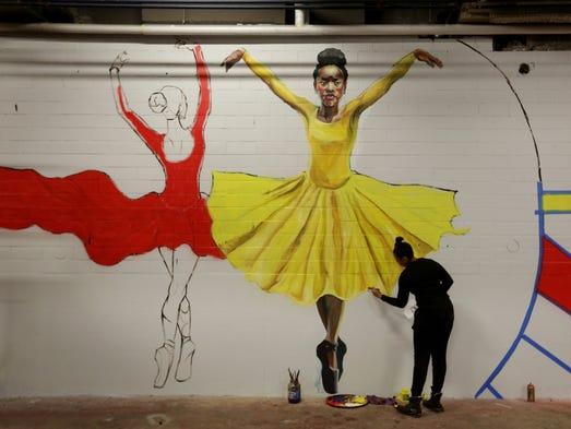 Artist Sydney G. James paints a mural inside the Federal