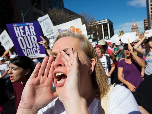 A demonstrator chants as she marches in downtown Austin