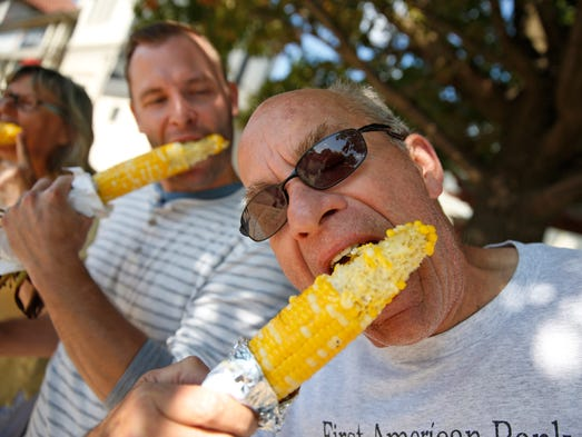 Doug Law, right, from Indianapolis chomps down on hot