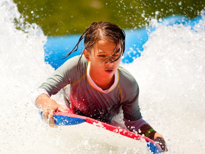 Bennet Crews, 13, rides a boogie board on the Flowrider in Cityscape, Aug. 24, 2014.
