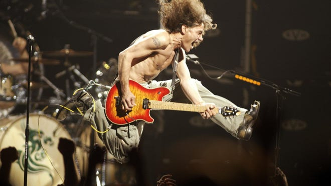 """Eddie Van Halen plays the final chord of """"Jump"""" during the Van Halen concert at the Continental Airlines Arena in East Rutherford, New Jersey, June 22, 2004. The legendary guitar virtuoso has died at age 65."""