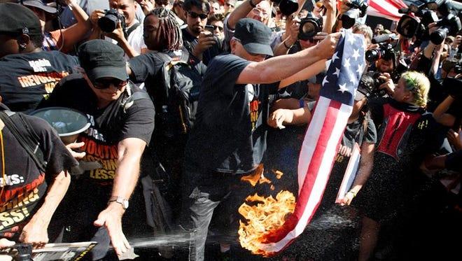 Un grupo de manifestantes quema una bandera de EE.UU. cerca a la entrada a Quicken Loans Arena, sitio donde se realiza la Convención Nacional Republicana, el 20 de julio de 2016, en Cleveland, Ohio (EE.UU.).