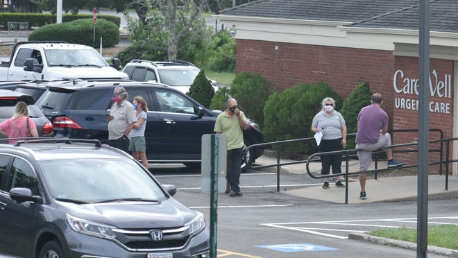 The parking lot fills with cars, many with out-of-state license plates, as people line up Wednesday morning outside CareWell Urgent Care in South Dennis for a rapid response COVID-19 test.