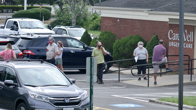 The parking lot is filled with cars at Patriot Square as patients queue up outside the Carewell Urgent Care for a COVID-19 test, Wednesday, Aug. 5, 2020, in Dennis, Mass.