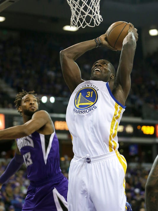 Golden State Warriors center Festus Ezeli, right, of Nigeria, goes to the basket against Sacramento Kings forward Derrick Williams during the first quarter of an NBA basketball game in Sacramento, Calif., Wednesday Oct. 29 2014.(AP Photo/Rich Pedroncelli)