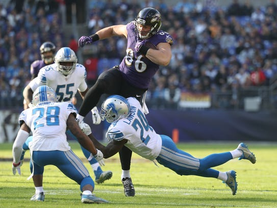 Ravens tight end Nick Boyle leaps over Lions cornerback Nevin Lawson in the first quarter in Baltimore on Sunday.