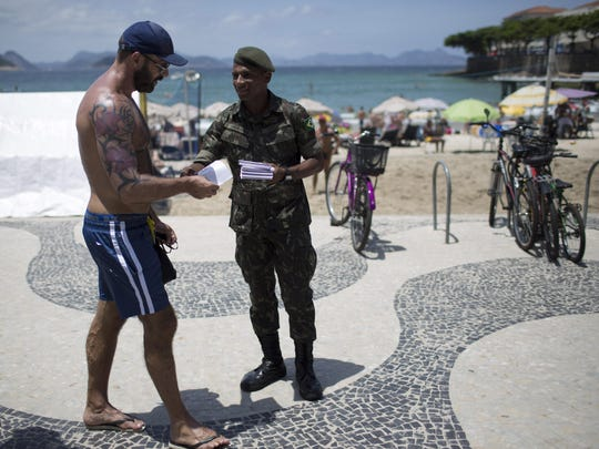 A soldier, on the edge of the Copacabana beach in Feburary in Rio de Janeiro, distributes a pamphlet about the Aedes aegypti mosquito, which spreads the Zika virus. Part of the beach will be used for the beach volleyball competition during the 2016 summer games.