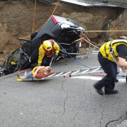 Firefighters pull an injured motorist from a trapped