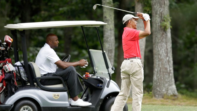 President Obama follows through on a swing as former NBA basketball player Alonzo Mourning looks on at Farm Neck Golf Club in Oak Bluffs, Mass., on Aug. 23, 2014.