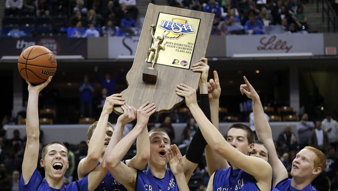 Greensburg High School players hold up their championship trophy after defeating Bowman Academy in the IHSAA Class 3A Indiana state boys' basketball championship game in Indianapolis.