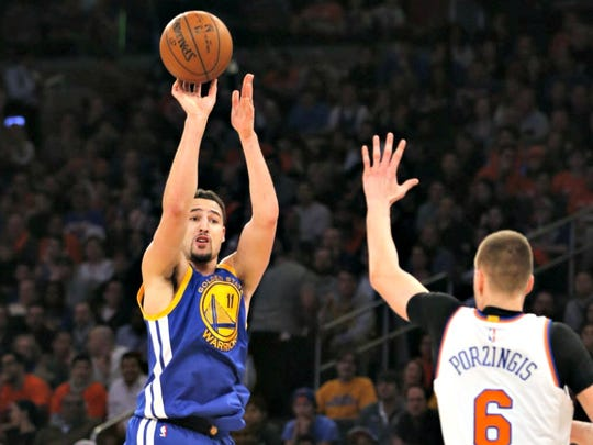 Golden State Warriors guard Klay Thompson shoots as Knicks forward Kristaps Porzingis defends.