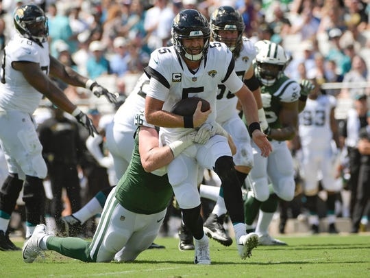 Jacksonville Jaguars quarterback Blake Bortles (5) is sacked by New York Jets defensive end Henry Anderson, left, during the first half of an NFL football game, Sunday, Sept. 30, 2018, in Jacksonville, Fla. (AP Photo/Phelan M. Ebenhack)