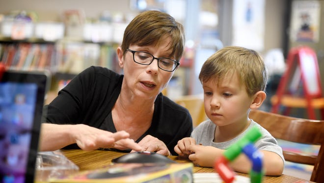 Palmyra's children's librarian Amy Shaffer-Duong helps Rhett Spittler, 4, with a science toy during a children's program at the Palmyra Public Library Wednesday, Aug. 16.