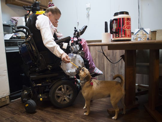 Sherri Kaspar hands her dog, Nala, a bone at her home in Kersey on Thursday, May 18, 2017. Kaspar had an operation performed by Ken Pettine at McKee Medical Center in Loveland in 1991 for injuries sustained in a car crash. Kaspar said after the surgery, she lost the use of her legs, and suffered an infection in her back, following the procedure.