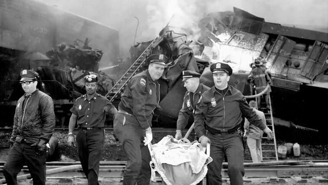 """Patrolmen carry one of the dead from the head on crash of two freight trains in a freight yard of the New York Central at West 146th Street. Six crewmen died and four more were injured, two seriously, in the unexplained disaster. Crewmen said that each train had clearance to use the same track. Mayor Lindsay, who flew to crash scene by helicopter, said: """"It shouldn't have happened. This is about as bad as you will find. I guess."""" Asked about a possible investigation, he replied: """"As soon as we get the facts, we'll decide what to do."""" May 22, 1967"""