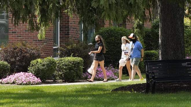 Students walk by Ritchie Dining Hall on Sept. 1 on the campus of Adrian College. The college reported Friday that the number of active COVID-19 cases on campus continues to fall.